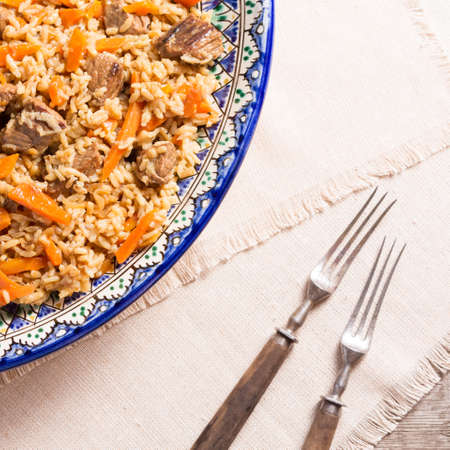 Pilaf in the handmade plate with antique forks on the wooden background. Square