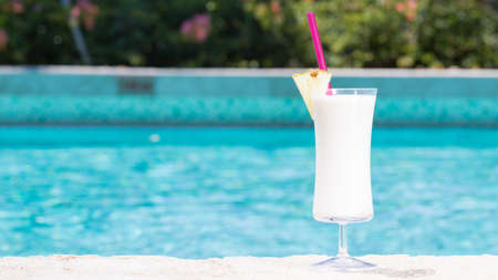 wide screen: Glass of Pina Colada cocktail on the pool nosing at the tropical resort. Horizontal, wide screen, cocktail on right side Stock Photo