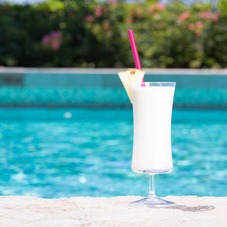 pina: Glass of Pina Colada cocktail on the pool nosing at the tropical resort. Square, cocktail on right side