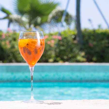 spritz: Glass of Aperol Spritz cocktail on the pool nosing at the tropical resort. Square, cocktail on left side