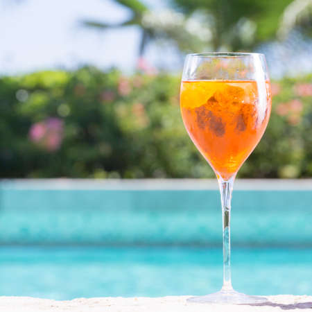 Glass of Aperol Spritz cocktail on the pool nosing at the tropical resort. Square, cocktail on right side Stock Photo