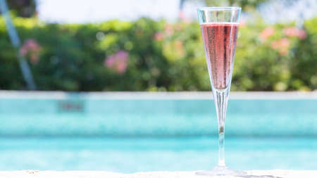 wide screen: Glass of Kir Royal cocktail on the pool nosing at the tropical resort. Horizontal, wide screen, cocktail on right side