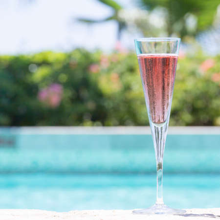 Glass of Kir Royal cocktail on the pool nosing at the tropical resort. Square, cocktail on right side