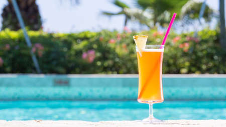 wide screen: Glass of Mai Tai cocktail on the pool nosing at the tropical resort. Horizontal, wide screen, cocktail on right side
