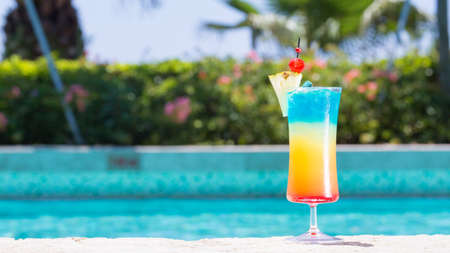 Glass of Rainbow cocktail on the pool nosing at the tropical resort. Horizontal, wide screen, cocktail on right side