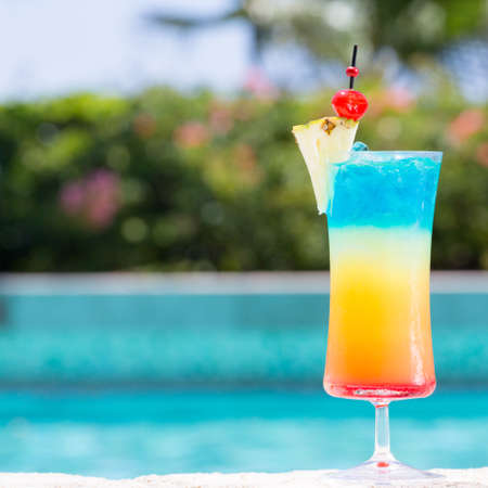 Glass of Rainbow cocktail on the pool nosing at the tropical resort. Square, cocktail on right side
