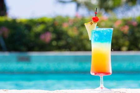 Copa de cóctel del arco iris en la piscina husmeando en el resort tropical. Horizontal, cóctel en el lado derecho Foto de archivo - 43527603