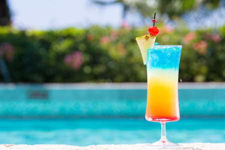 Glass of Rainbow cocktail on the pool nosing at the tropical resort. Horizontal, cocktail on right side