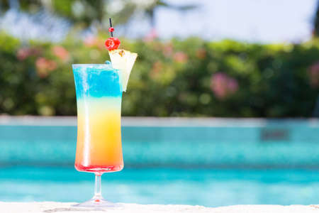 Glass of Rainbow cocktail on the pool nosing at the tropical resort. Horizontal, cocktail on left side