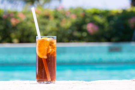cocteles: Copa de Cuba Libre en la piscina husmeando en el resort tropical. Horizontal, c�ctel en el lado izquierdo