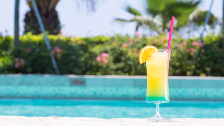 wide screen: Glass of Happy days non alcohol cocktail on the pool nosing at the tropical resort. Horizontal, cocktail on right side, wide screen Stock Photo