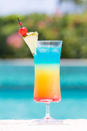 rainbow cocktail: Glass of Rainbow cocktail on the pool nosing at the tropical resort. Vertical