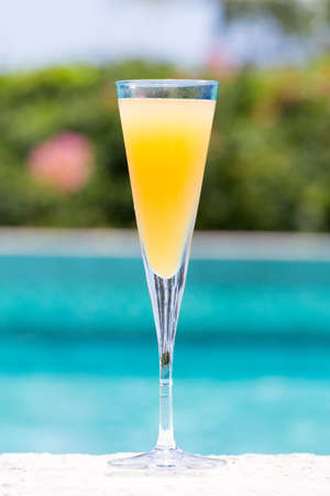 bellini: Glass of Bellini cocktail on the pool nosing at the tropical resort. Vertical Stock Photo