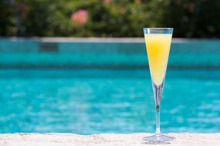 Glass of Mimosa cocktail on the pool nosing at the tropical resort. Horizontal, cocktail on right side