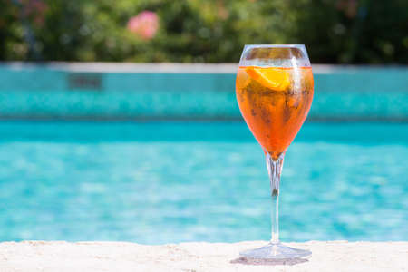 pool party: Glass of Aperol Spritz cocktail on the pool nosing at the tropical resort. Horizontal, cocktail on right side Stock Photo
