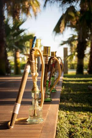 waterpipe: Hookah, traditional arabic waterpipe, in the arabic restaurant. Vertical, direct sunset light, outdoor photo