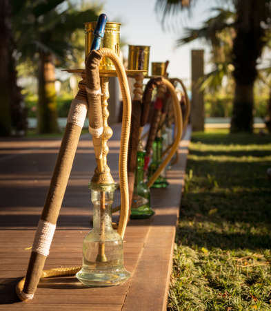 waterpipe: Hookah, traditional arabic waterpipe, in the arabic restaurant. Square, direct sunset light, outdoor photo Stock Photo