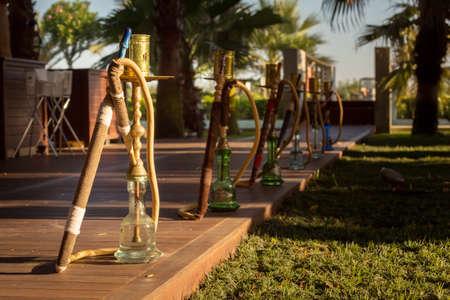 waterpipe: Hookah, traditional arabic waterpipe, in the arabic restaurant. Horizontal, direct sunset light, outdoor photo Stock Photo