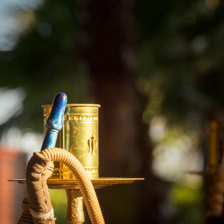 waterpipe: Part of hookah, traditional arabic waterpipe, in the arabic restaurant. Square, direct sunset light, outdoor photo