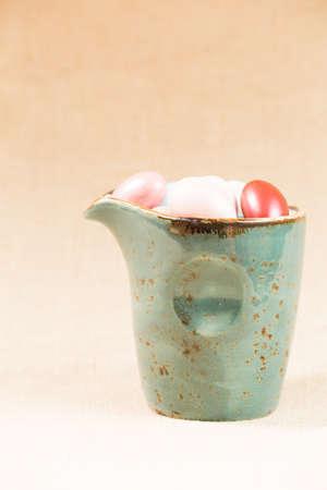 jag: Variety of chocolate eggs in milk jar. Blue jar. Vertical Stock Photo