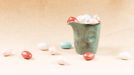 wide screen: Variety of chocolate eggs in milk jar and on the table. Blue jar. Horizontal, wide screen