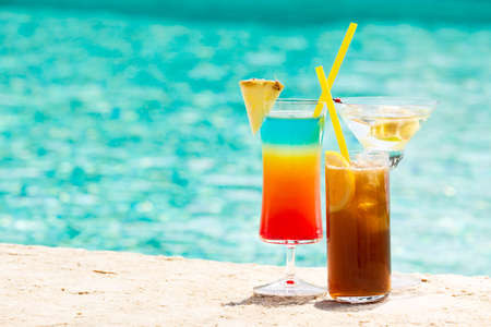 Three summer cocktail by pool. Delicious beverages. Horizontal Banco de Imagens