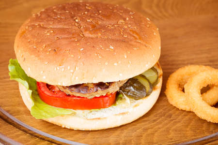 onion rings: Classic homemade hamburger with onion rings on a wooden plate. Juicy homemade food. Horizontal