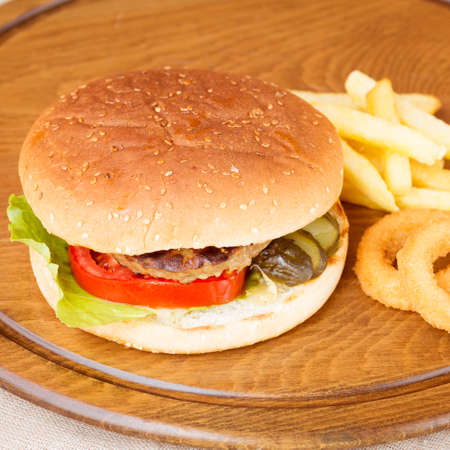 onion rings: Classic homemade hamburger with onion rings and french fries on a wooden plate. Juicy homemade food. Square