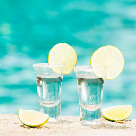 Two tequila shots with sliced lime on the beach. Transparent alcohol. Hanging out. Square