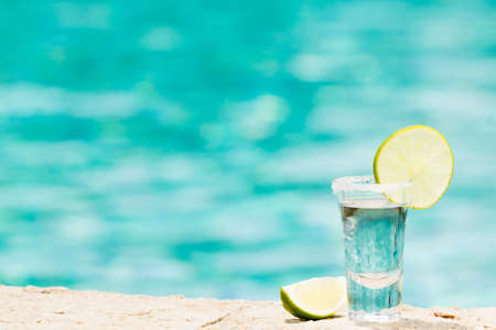 One tequila shot with sliced lime on the beach. Transparent alcohol. Hanging out. Horizontal, shot at the right side