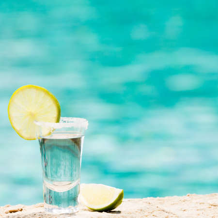 alcohol: One tequila shots with sliced lime on the beach. Transparent alcohol. Hanging out. Square
