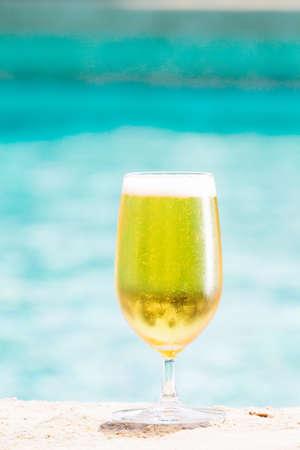 caballo bebe: Vaso de cerveza en la playa. alcohol transparente. Pasando el rato. Vertical