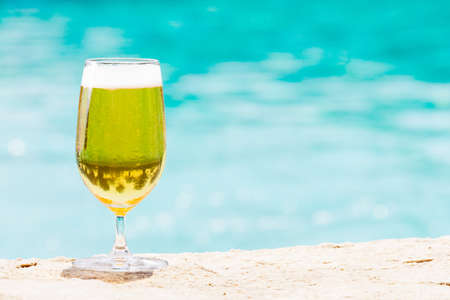 horse collar: Glass of beer on the beach. Transparent alcohol. Hanging out. Horizontal, glass on the left side
