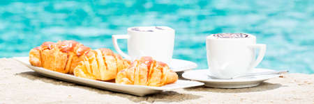 side plate: Side view of cafe latte with topping on it. Standing on sand with croissants on white plate. Horizontal, banner