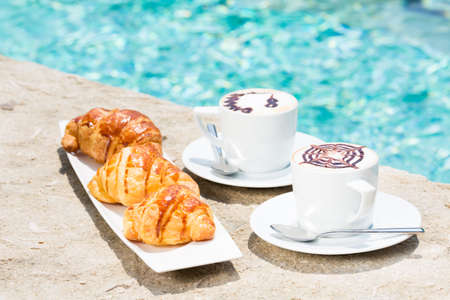 side plate: Side view of cafe latte with topping on it. Standing on sand with croissants on white plate. Horizontal