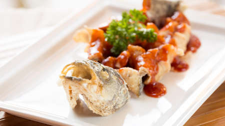 far east: Japanese style fried sea bass, served with sweet and sour sauce. Far east restaurant cuisine. Horizontal, wide screen format Foto de archivo
