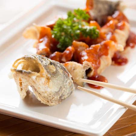 lejano oriente: frito estilo japon�s lubina, servido con salsa agridulce. Con palos. Lejano oriente restaurante de cocina. Cuadrado