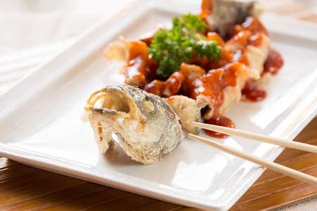 lejano oriente: frito estilo japon�s lubina, servido con salsa agridulce. Con palos. Lejano oriente restaurante de cocina. Horizontal Foto de archivo