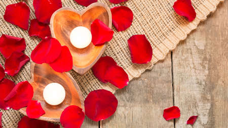 Enlightened candles in heart-shaped candleholders with red roses petals on rustic wooden background. St Valentines background. Romantic holiday concept. Top view. Horizontal. Wide screen format