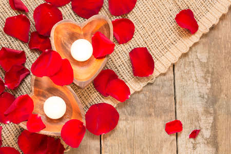 candleholders: Enlightened candles in heart-shaped candleholders with red roses petals on rustic wooden background. St Valentines background. Romantic holiday concept. Top view. Horizontal