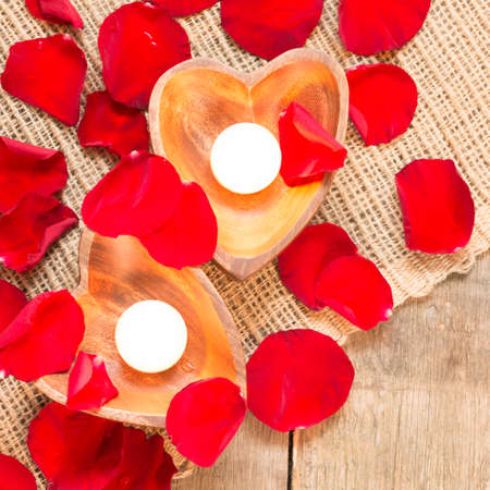 candleholders: Enlightened candles in heart-shaped candleholders with red roses petals on rustic wooden background. St Valentines background. Romantic holiday concept. Top view. Square