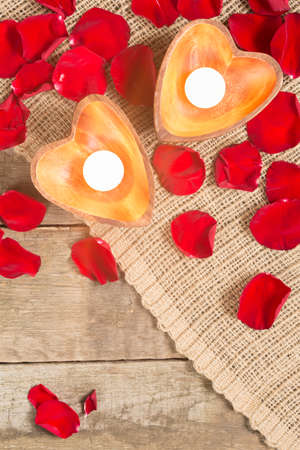 Enlightened candles in heart-shaped candleholders with red roses petals on rustic wooden background. St Valentines background. Romantic holiday concept. Top view. Vertical. Copy space at lower part