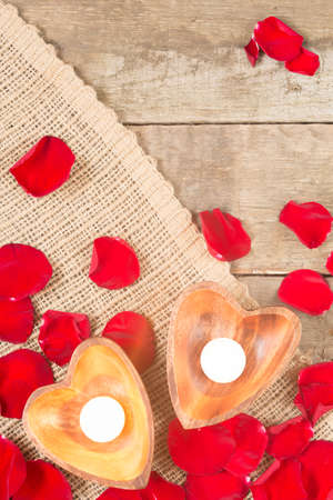 Enlightened candles in heart-shaped candleholders with red roses petals on rustic wooden background. St Valentines background. Romantic holiday concept. Top view. Vertical. Copy space at upper part