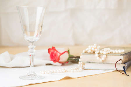 vaso vacio: Beautiful empty glass  with vintage books and pearls. Lightweight background. Vintage style. Horizontal