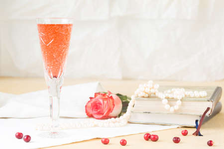 royale: Glass of kir royal cocktail with vintage books and pearls. Lightweight background. Vintage style. Horizontal