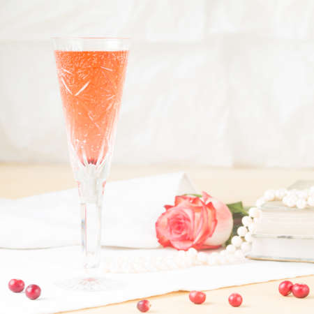 Glass of kir royal cocktail with vintage books and pearls. Lightweight background. Vintage style. Square