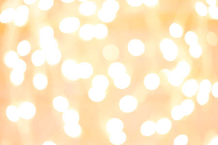 Holiday background with white blurred defocused bokeh. Christmas background. Horizontal. Yellow warm tone
