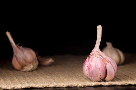 ajo: bulbo de ajo rosa en el fondo oscuro. superficie rústica. Con otras bombillas en el fondo. Horizontal