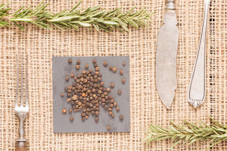 Black peppercorns on dark plate with rosemary, antique forks, spoon and knife. Rustic background. Warm color. Horizontal Stock Photo