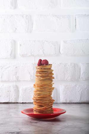 maslenitsa: Stack of pancakes with raspberries on top. Homemade dessert. Maslenitsa concept. White brick background. Vertical
